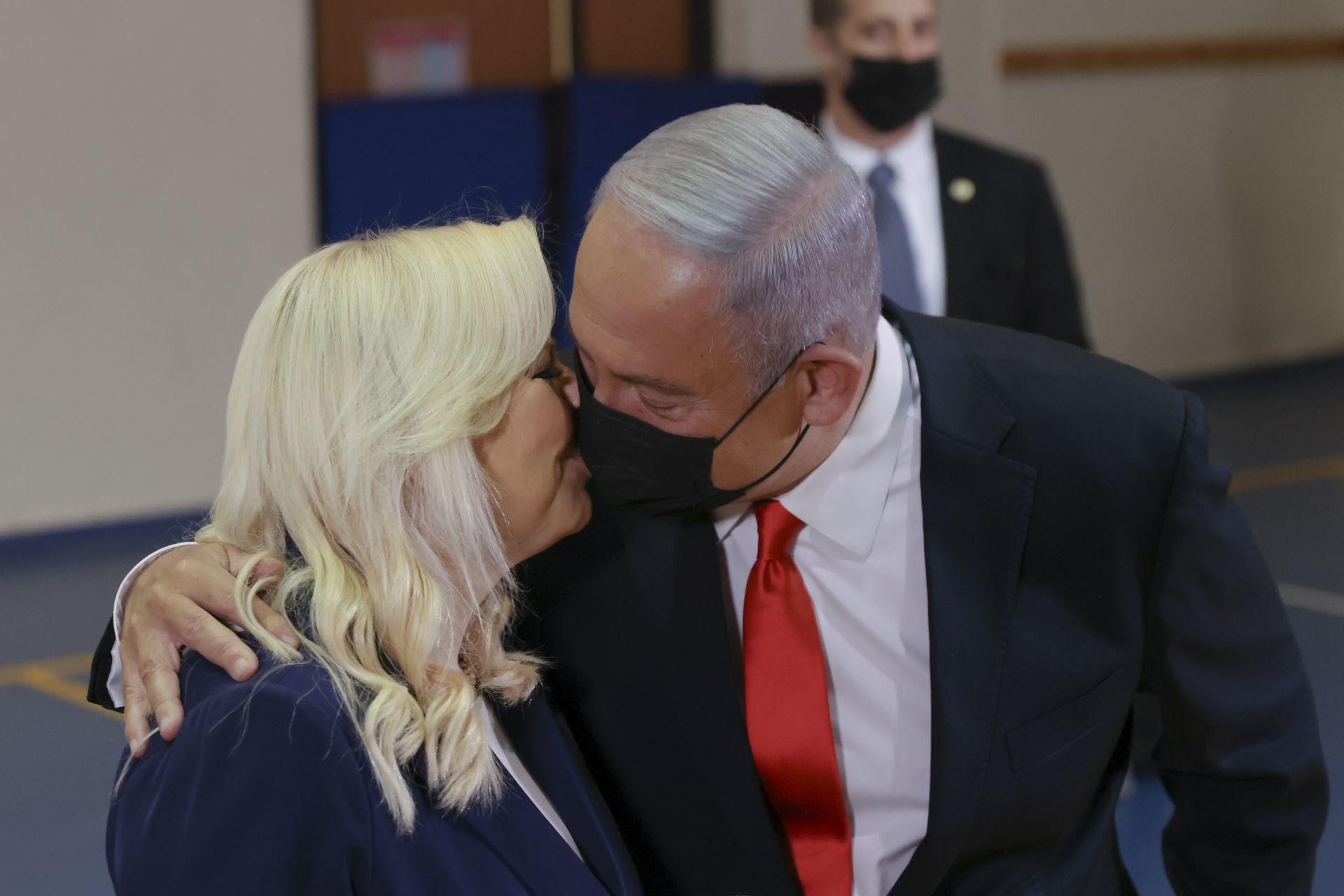 Бенямин Нетаняху целува съпругата си Сара през маската, след като гласуваха