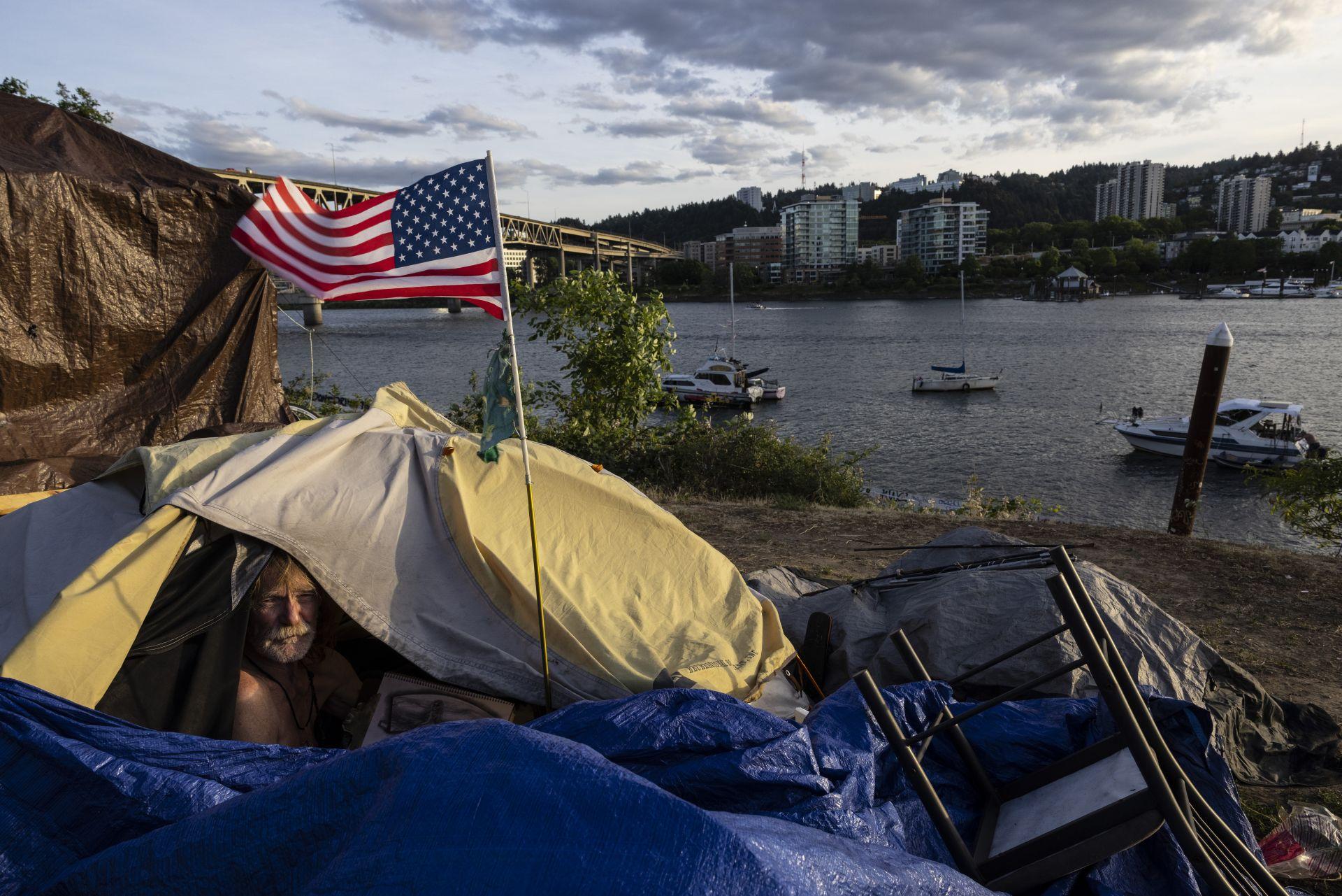 10 юни 2021 г. - Бездомникът Франк стои в палатката си с изглед към реката в Портланд, Орегон. Протестите след убийството на Джордж Флойд, нарастването на смъртта от въоръжено насилие и все повечето бездомници предизвикват въпроса, дали най-големият град в Орегон може да се възстанови.