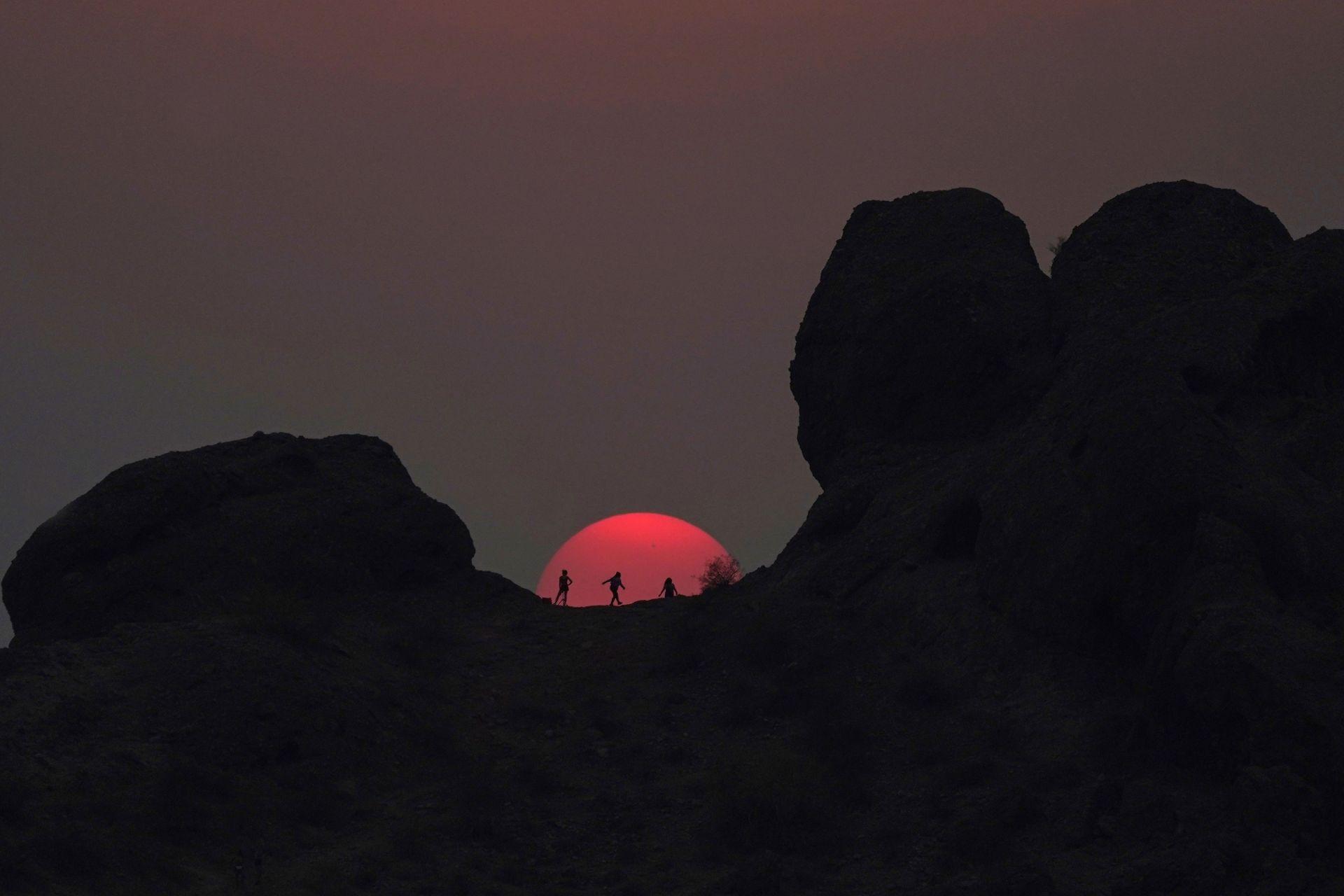 12 юни 2021 г. - Туристи наблюдават залеза в Папаго Парк, Финикс, по време на горещата вълна с температури до 46 градуса
