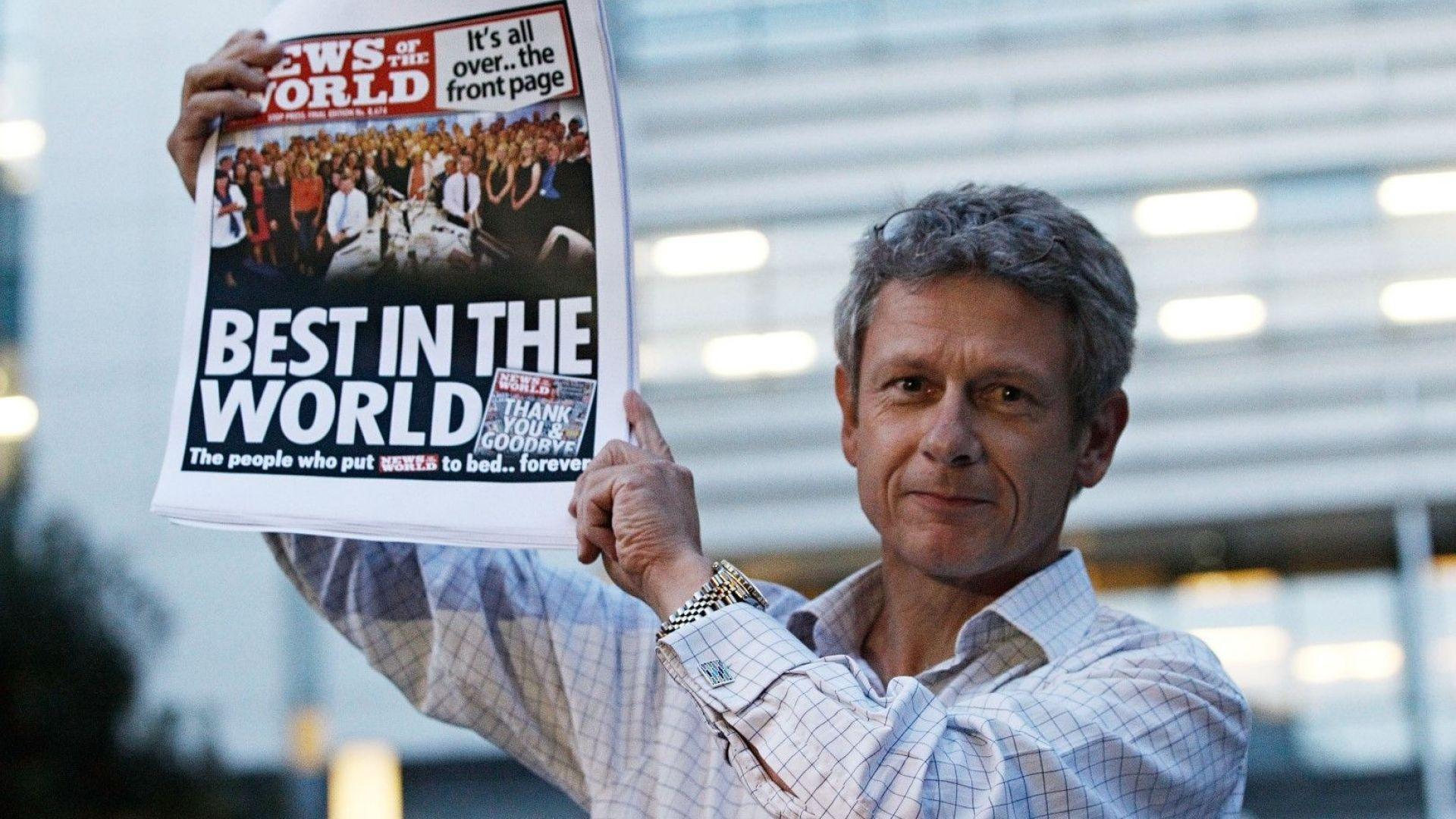 Редакторът на News of The World Хари Скот показва специалното издание на вестника, отпечатано за членовете на редакцията в последния ден на вестника, застанал пред офисите на издателя News International, 9 юли 2011 г.