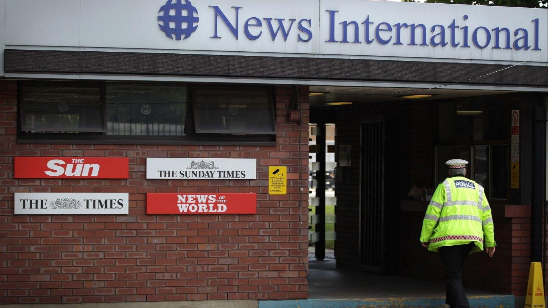 Полицай влиза в централата на издателя News International на 7 юли 2011 г. След сериозни твърдения, че хакерството на телефони е широко разпространено в News of the World, изпълнителният директор Джеймс Мърдок обяви, че вестникът ще бъде закрит