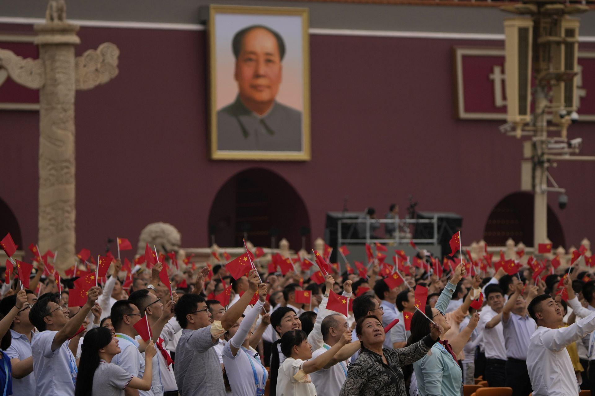Хората развяват китайски знамена под голям портрет на покойния лидер Мао Дзедун по време на церемония по повод 100-годишнината от основаването на управляващата китайска комунистическа партия на портата Тянанмън в Пекин