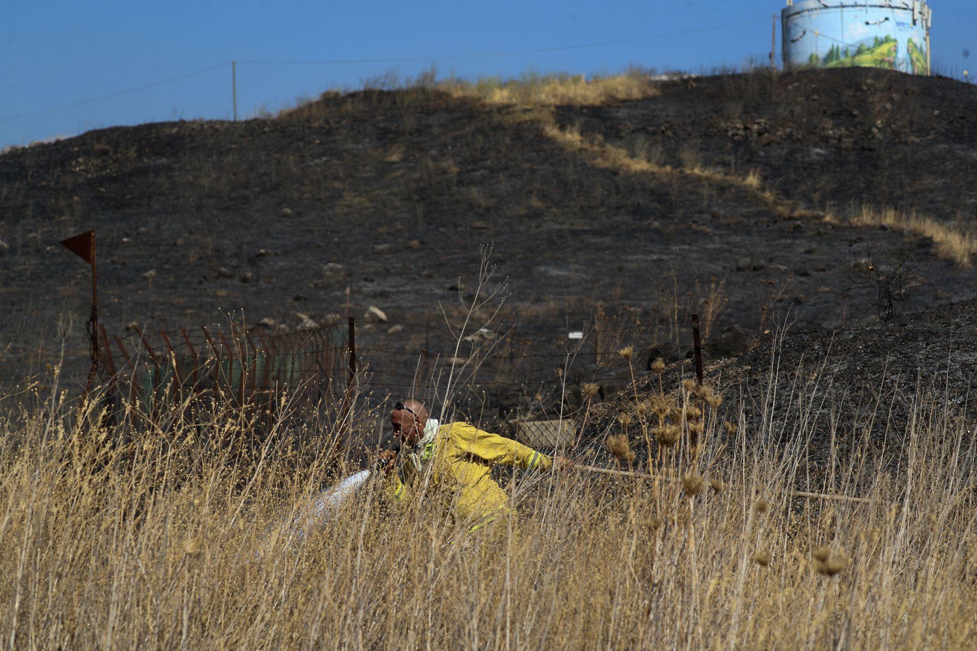Израелски пожарникар се опитва да потуши пожар, причинен от ракета, изстреляна от Ливан в израелска територия в близост до северния израелски град Кириат Шмона,