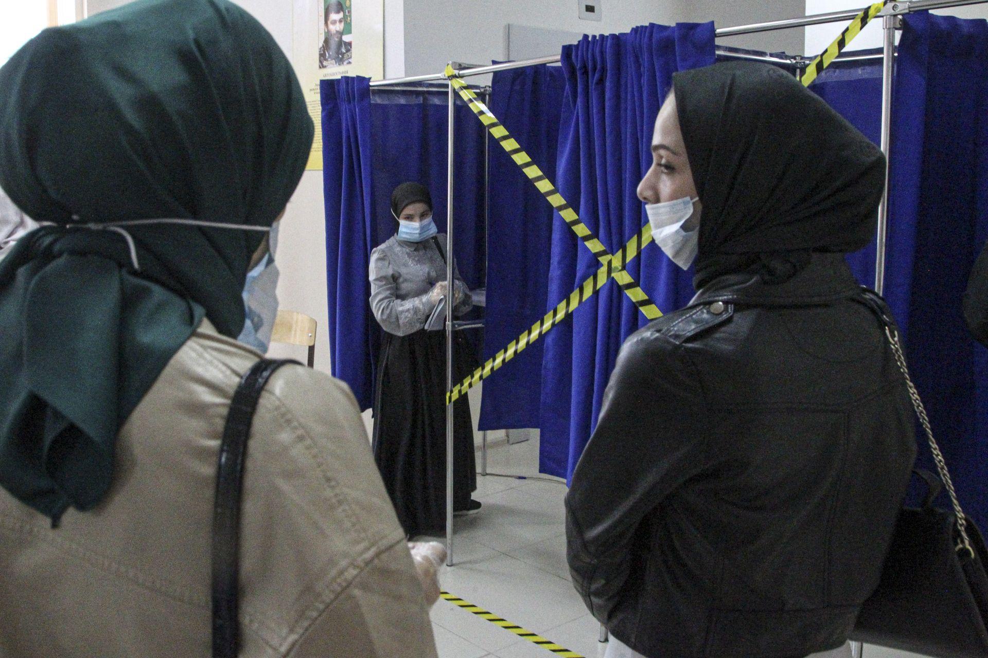 Чеченските жени чакат да попълнят бюлетините си в кабината за гласуване на избирателна секция по време на парламентарните избори в Грозни